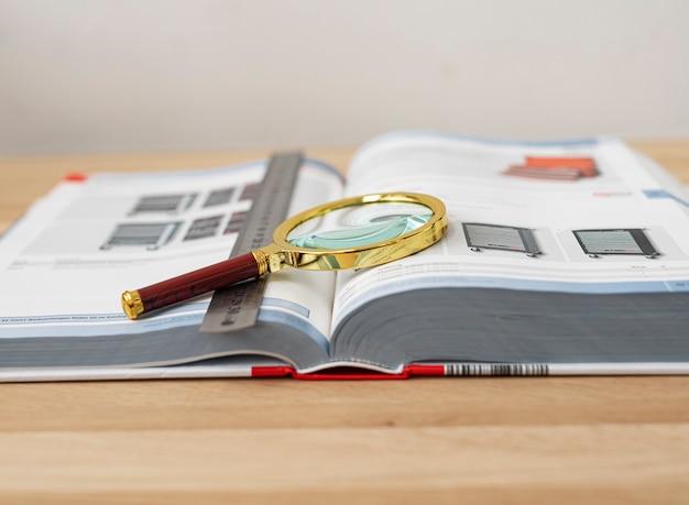 木製の机の上に拡大鏡と定規を使って勉強するための技術書を開きます。