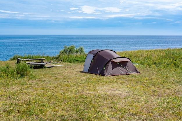 Открытая палатка в туристическом месте отдыха со скамейками и столом на траве у озера байкал. голубое небо с облаками и летним солнцем.