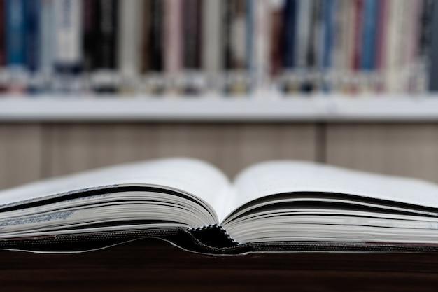 Открыть учебник на столе в библиотеке с фоном книжных полок