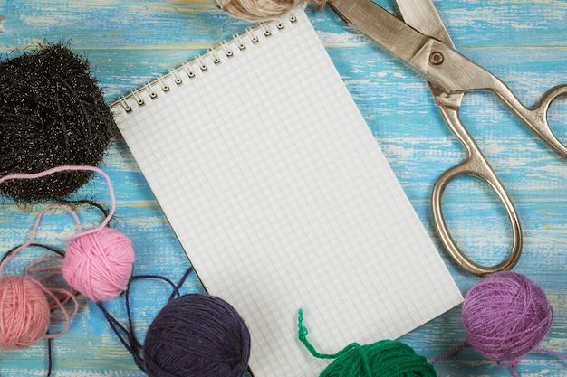 ノートブックを開き、青い木製のテーブルに裁縫用に設定します。