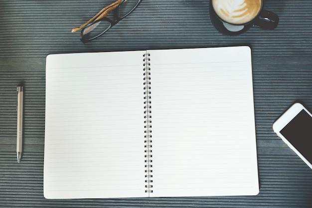 페이지 메모장을 엽니 다. 사무실 책상 테이블에는 책, 전화, 업무용 장비 공급 및 커피 컵이 있습니다.