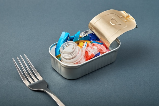 Open tin can and fork. plastic waste instead of fish inside. ocean plastic pollution concept
