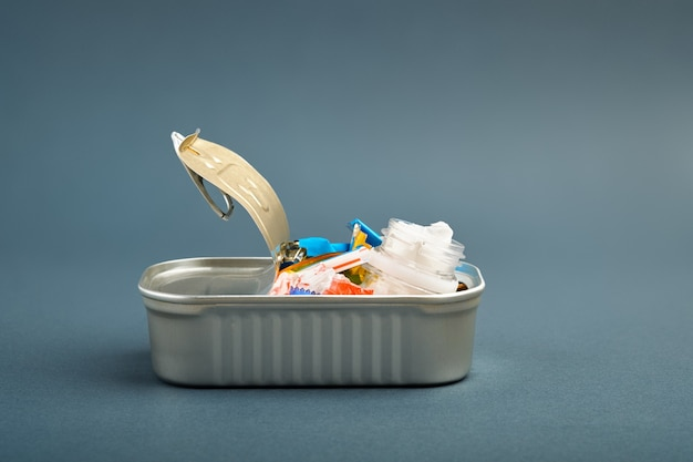 Open tin can. plastic waste instead of fish inside. ocean plastic pollution concept
