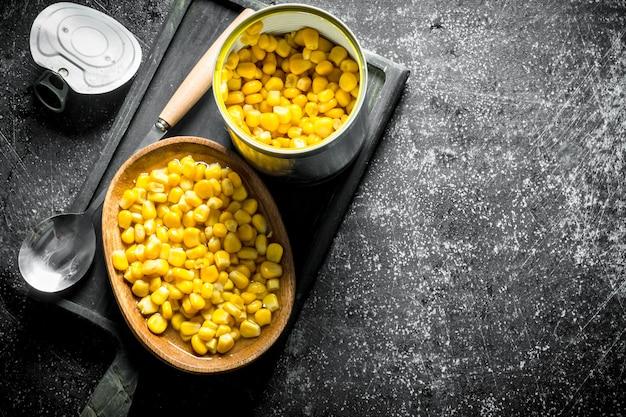 暗い木製のテーブルのまな板に缶詰のトウモロコシと缶を開ける
