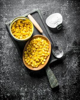 まな板の上に缶詰のトウモロコシが入った缶を開けます。暗い素朴な表面に