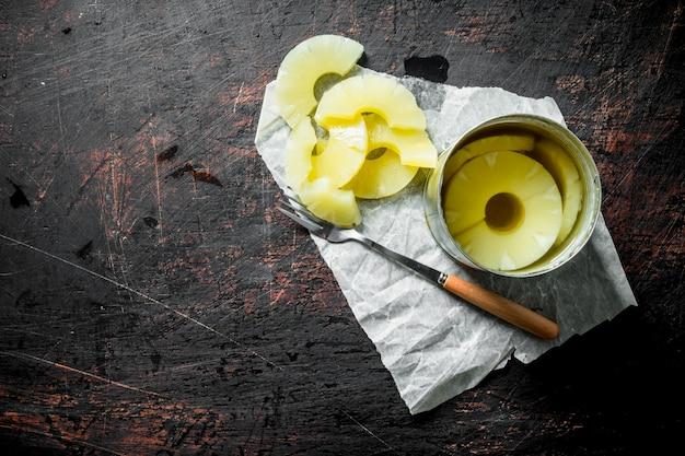 暗い木製のテーブルに缶詰のパイナップルと缶を開ける