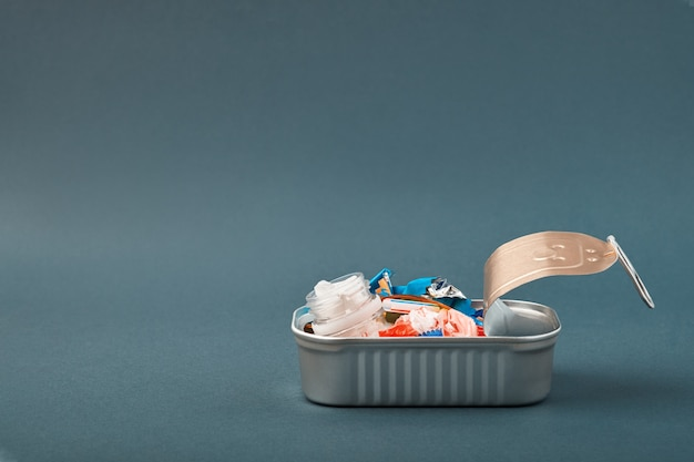 Open tin can with plastic waste instead of fish inside