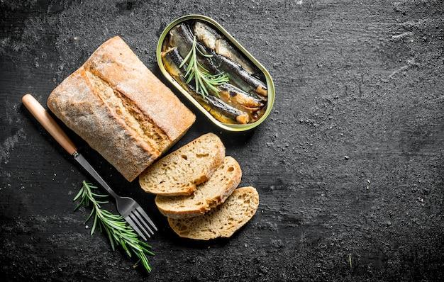 Sprats와 얇게 썬 빵과 함께 열린 깡통. 검은 소박한 표면에