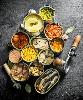 Откройте консервные банки с ананасами, кукурузой, грибами и шпротами. на черном деревенском фоне
