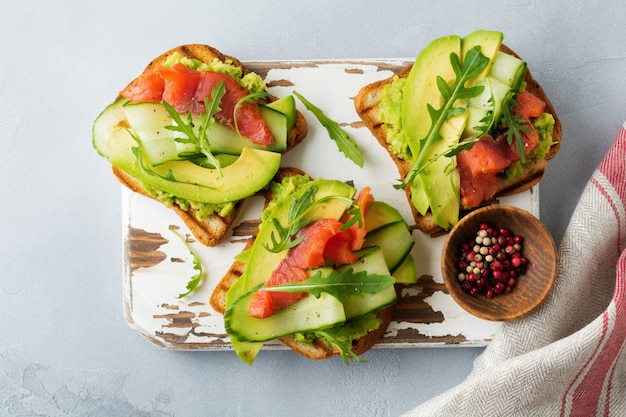 Open toast with trout, salmon, avocado, cucumber and arugula on wooden stand on gray concrete background. selective focus. top view. copy space
