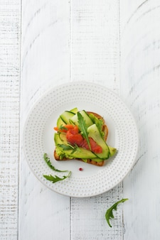 Open toast with trout, salmon, avocado, cucumber and arugula on wooden stand on white wooden table background. selective focus. top view. copy space