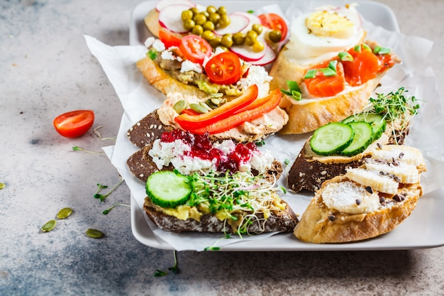 Open toasts with different toppings on gray-brown background