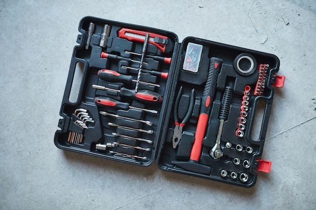 Open tool box with red hammer and screwdriver on concrete floor at construction site, copy space