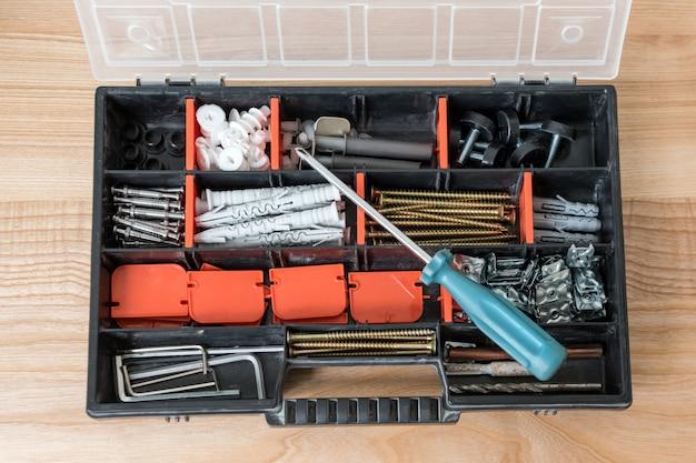 さまざまな器具、ネジ、ドライバーでツールボックスを開く