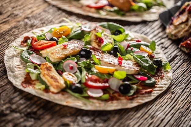Вегетарианская лепешка с открытым верхом с салатом, редисом, помидорами черри, оливками, гранатом и жареным сыром халуми.