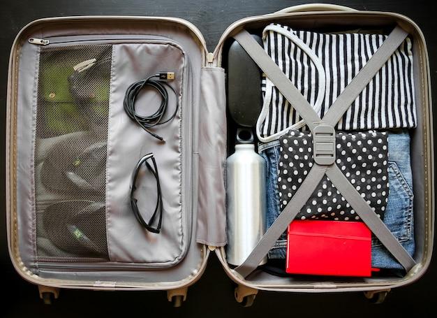 黒の背景に分離された服でいっぱいのオープントラベルスーツケース