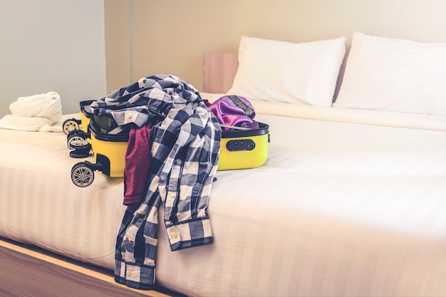 Open travel suitcase with clothes and accessories on bed