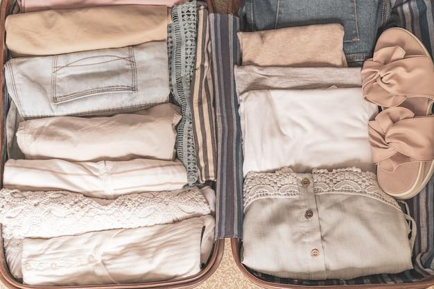 服やアクセサリー、旅行や休暇の概念と旅行者のバッグを開く