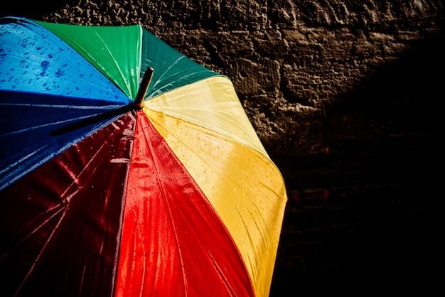 Открытый зонт против яркого солнца с яркими цветами и темным фоном.