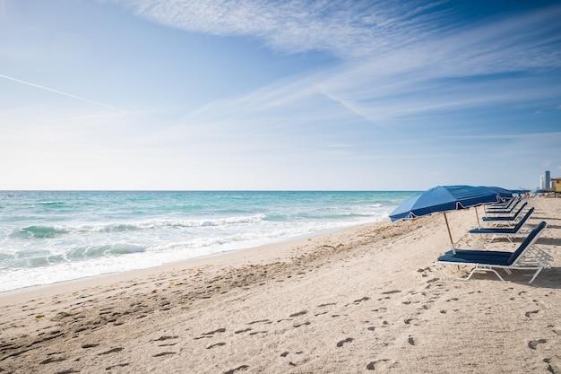 Открытые зонтики на пустом песчаном пляже у океана на фоне голубого неба