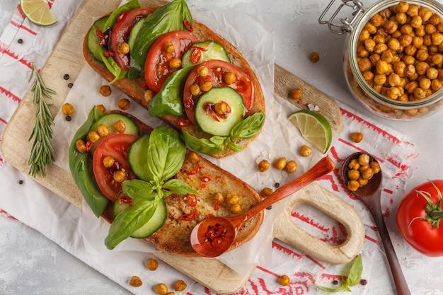 トマト、キュウリ、揚げひよこ豆、バジル、トップビューでベジタリアンサンドイッチを開きます。健康的なビーガンフードのコンセプトです。