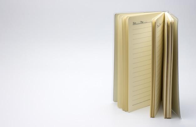 コピースペースで白い背景の上の垂直の空のノートブックを開きます