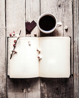 Open vintage book with blossom branch of cherry tree, chocolates and coffee cup