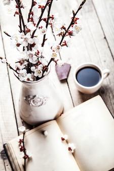 美しいヴィンテージの花瓶と一杯のコーヒーと木製のテーブルに桜の木の花の枝でヴィンテージの本を開く