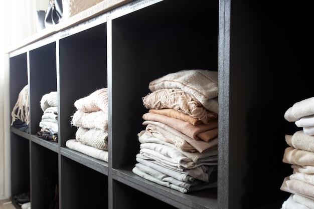 접힌 옷이 많이 있는 오픈 옷장 정리된 옷장과 쌓인 옷이 있는 현대적이고 깨끗한...