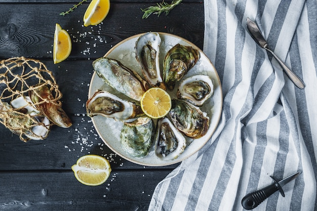 Open wet oysters on a plate with lemon