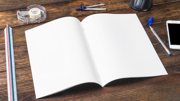 An open white blank paper with stationeries on wooden table