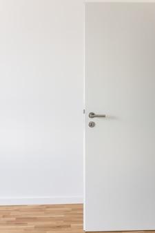 방의 흰 벽에 회색 크롬 손잡이와 열쇠 구멍이있는 흰색 문을 엽니 다.