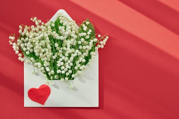 빨간색 배경에 사랑하는 사람들과 함께 흰색 봉투를 엽니다.