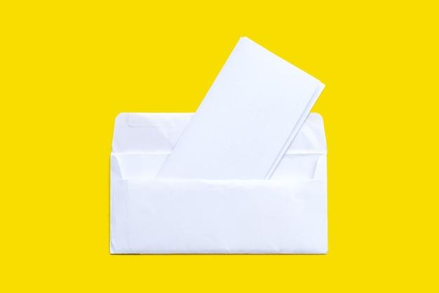 Открытый белый конверт с бумагой на желтой поверхности