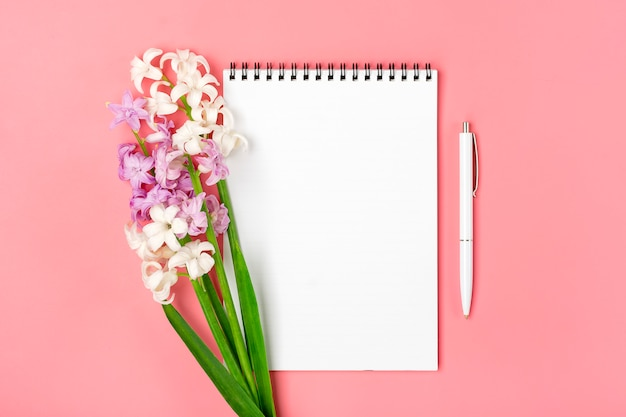 Open white notebook, pen, bouquet of hyacinths flowers on pink background flat lay