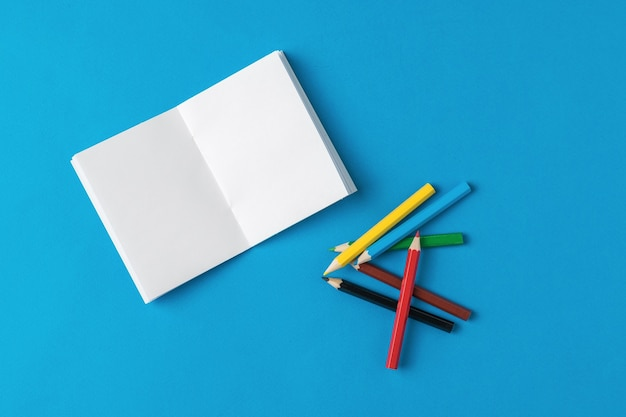 An open white notebook and a pile of pencils on a blue background. stationery and school supplies.