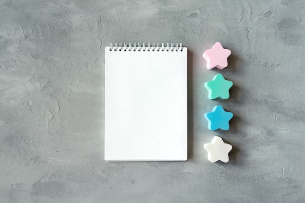Open white notebook with stars on gray concrete background