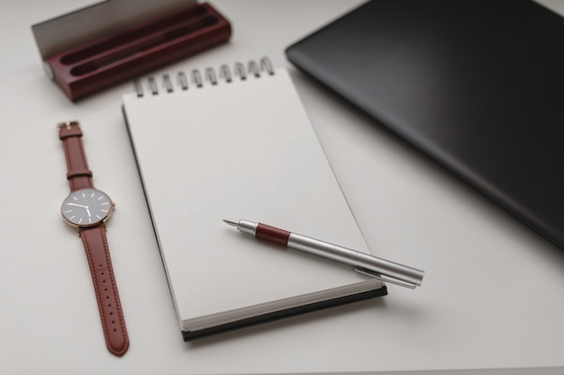 Open white spiral notebook with a blank sheet and a lot of office accessories, a wrist watch, mobile phone , pen case and a laptop.