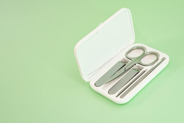 ステンレス製のはさみ、2つの爪切り、足ひれ、耳かきが入った白い収納ボックスを、薄緑色の背景に置きます。
