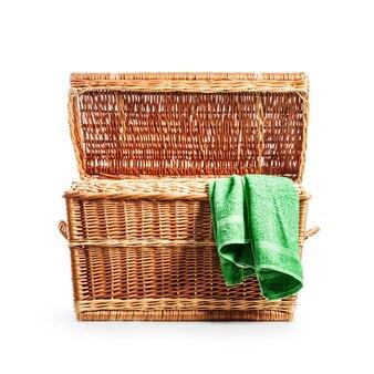 籐の洋服ボックスを開きます。緑のタオルが付いている洗濯かご。宝箱。クリッピングパスで白い背景に分離されたオブジェクト
