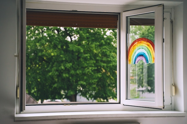 Open window in room with green trees on background painting rainbow on window