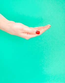 Open woman hand on isolated green color background