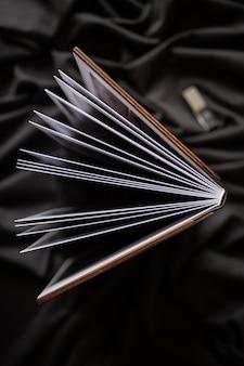검은 천으로 배경에 나무 책을 엽니 다.