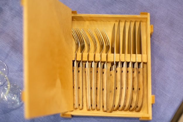 Открытый деревянный ящик со столовыми приборами, 6 ножей и шесть вилок на синей скатерти. вид сверху, крупный план, мягкий фокус