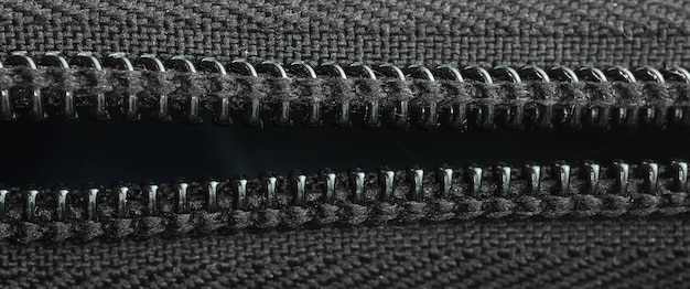 Open zipper on a black backpack, close-up textile, banner photo