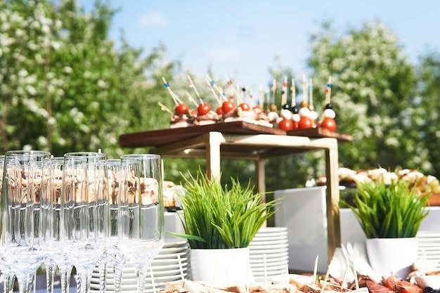 Фуршет на открытом воздухе с бокалами и холодными закусками перед началом праздника