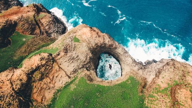 緑のカウアイ島のナパリ海岸にある美しいopenceiling海の洞窟の空撮