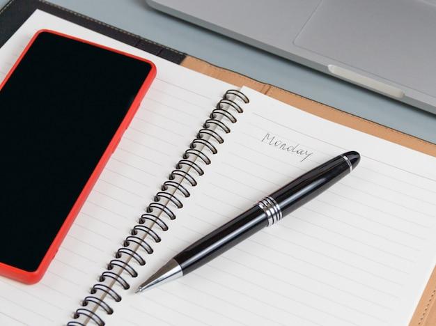 회색에 휴대 전화 및 노트북 근처에 필기 월요일로 열린 의제를 닫습니다.
