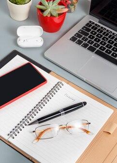 회색 책상에 노트북 근처 필기 월요일에 열린 의제를 닫습니다.