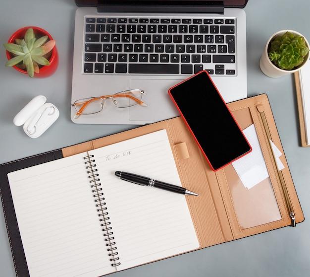 노트북 근처에 to do list라는 텍스트가 있는 열린 의제 및 회색 책상 상단 보기에 현대적인 가제트